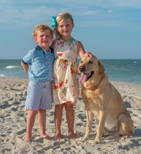 Image of two kids and a dog on a beach